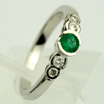 Explore traditional elegance with this emerald engagement ring by Keith Gordon